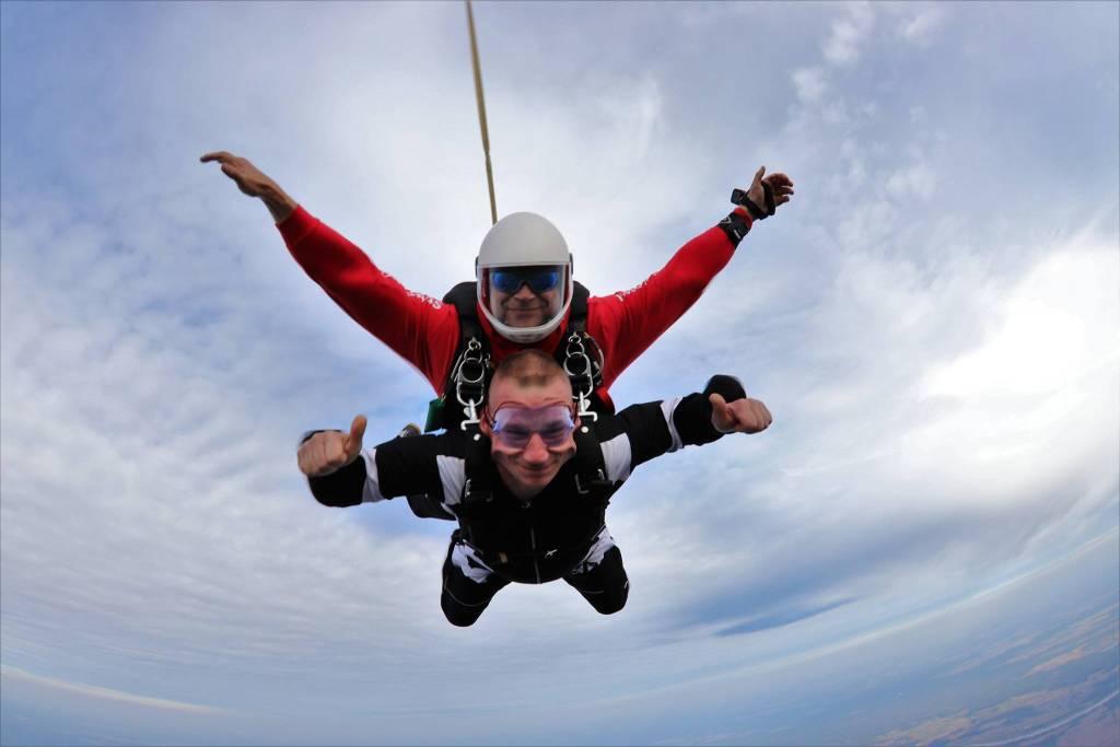 Dwóch mężczyzn leci w powietrzu i są przypięci do spadochronu.