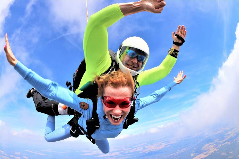 Dwie osoby skaczą ze spadochronem w tandemie.