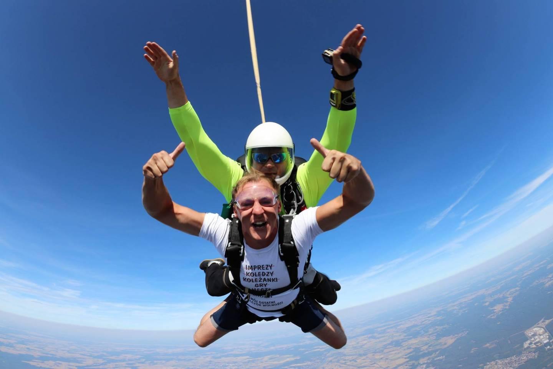 Dwóch radosnych mężczyzn skacze ze spadochronem.