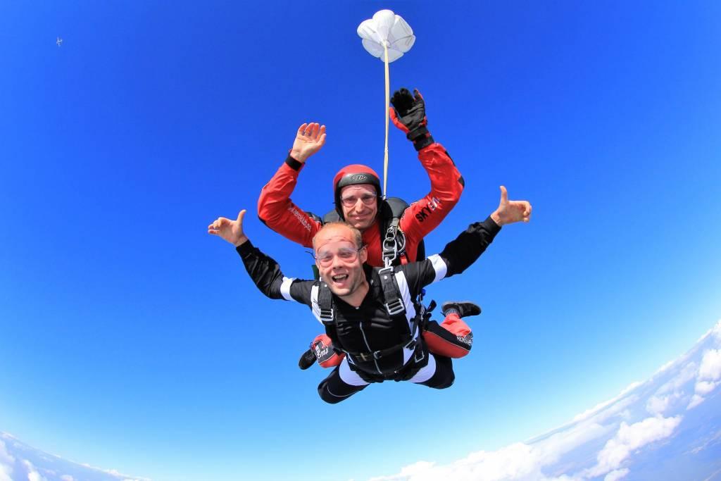 Dwóch mężczyzn skacze ze spadochronem - są ponad chmurami.