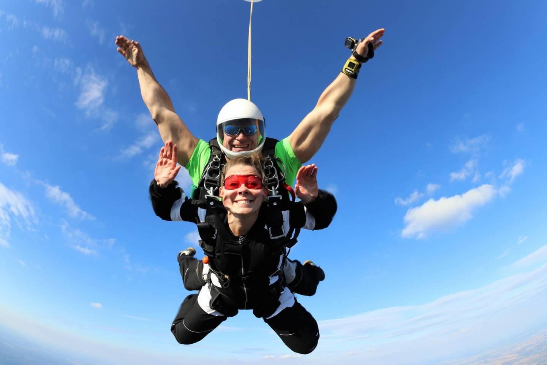 Kobieta i mężczyzna skaczący ze spadochronem w tandemie.