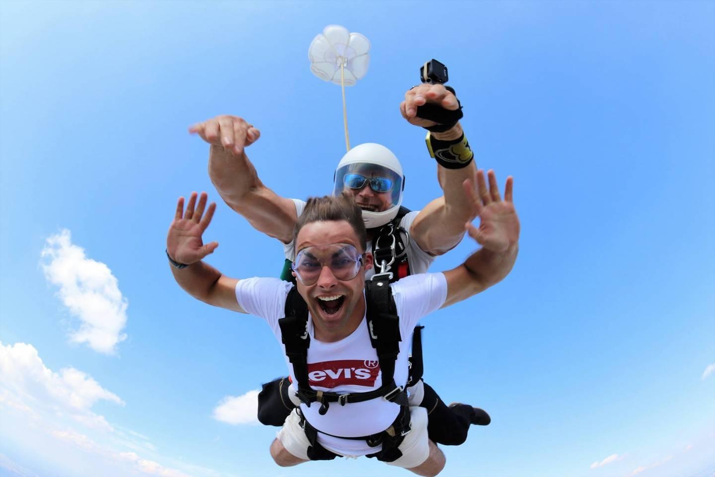 Dwóch mężczyzn skaczących ze spadochronem w tandemie w letni dzień.